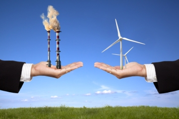 On the left a hand holding smoke stacks spewing fumes. On the right a hand holding wind turbines, both against the background of a strip of grass under a blue, mostly cloudless skiy.